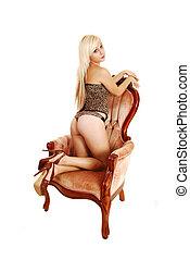 Girl kneeling in armchair. - A young pretty woman kneeling...