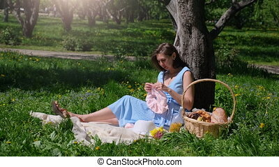 girl knits clothes in a Sunny Park near tree - girl resting...