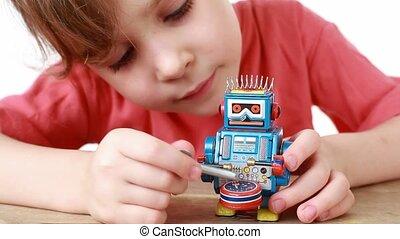 girl knocks winder on a drum of clockwork toy robot