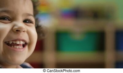 Young baby girl laughing, clapping hands and having fun at kindergarten