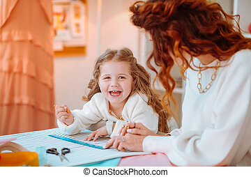 Girl laughing making sketches with mom working as designer