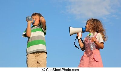 girl laughing through megaphone, boy drinking water and plugging up ear