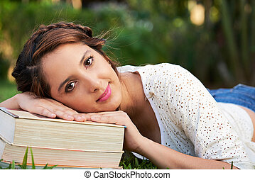 girl lay on top of books