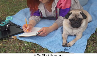 Girl laying on a lawn and writing, her pug laying beside