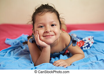 smiling latino girl laying on blye blanket bed