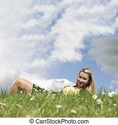 Girl laying on grass hill with copyspace sky