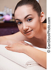 girl laying on massage table. girl is given massage of her back