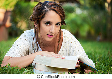 girl laying with books at the park