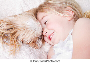girl laying with shih tzu dog
