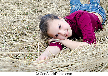 Girl lays on a dry grass