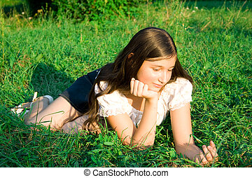 girl lays on a grass