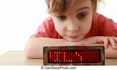 Girl lays on table near information LED display with word Family and smiles