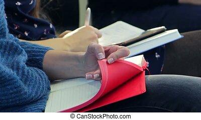 girl lazily scrolls notebook - Girl leafing through a...