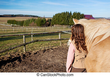 Girl leading her horse through the riding area