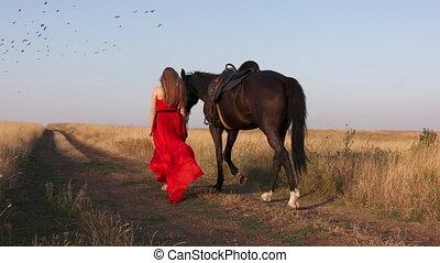 Girl leading horse walking down dirt road flock of ravens...