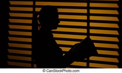 Girl leafing through a book. Book in the hands. Silhouette. Close up