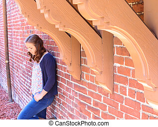 Girl Leaning Against Red Brick Wall