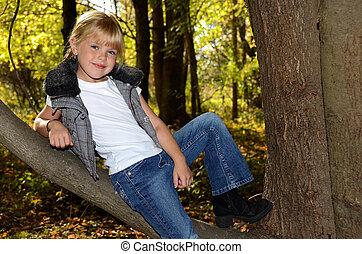 Girl leaning on tree limb