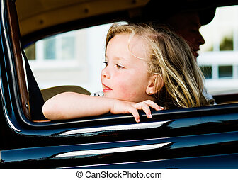 Girl leaning out the window of a car