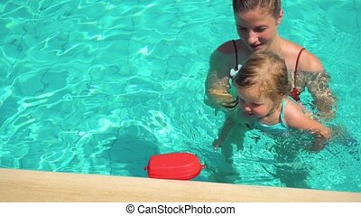 Girl learning how to swim with her mothers help - Mother...