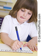 Girl learning to write numbers in primary class
