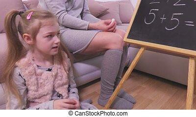 Girl learns to count near blackboard