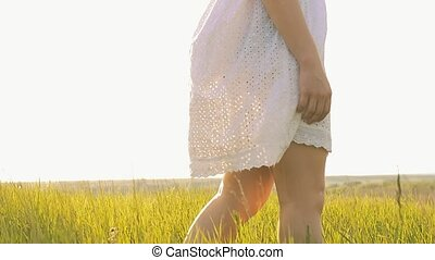 girl legs walking in the grass slow-motion video