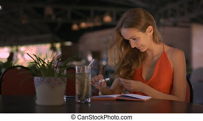 Girl Lets Long Hair down Sitting at Table in Cafe
