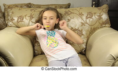 Girl licking candy on a stick in the form of lemon and raises the thumbs up