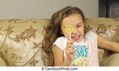 Girl licking candy on a stick in the form of lemon she was very sour