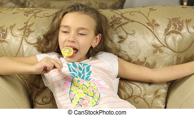 Girl licking candy on a stick in the form of lemon