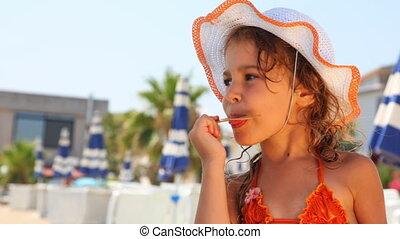 Girl licks stick from ice cream on beach