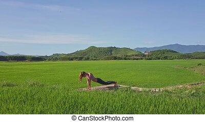 Girl Lies down in Yoga Pose among Countryside