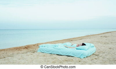 Girl lies on a bed at the sea beach?