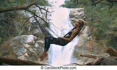 Girl Lies on Hammock against Pictorial Waterfall - closeup...