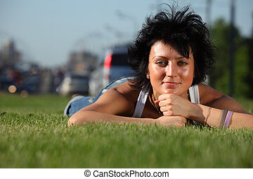 girl lies on lawn at road in city