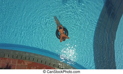 girl lies on lifebuoy in swimming pool and relax