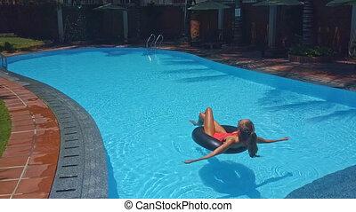 girl lies on ring sunbathing in pool
