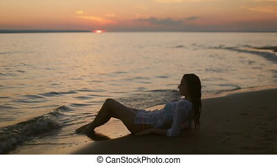 girl lies on the beach at sunset