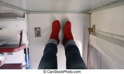 Girl lies on side bed in reserved seat of train car and put her legs on wall. Girl lying on side of bed in second-class train car and put his feet on wall. POV woman lies in blue jeans and red socks