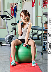 Girl lifting weights - Beautiful girl sitting on exercise...