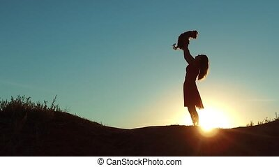 girl lifts a small dog at sunset silhouette. woman playing...