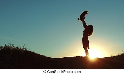 girl lifts a small dog sunset silhouette. woman playing with a dog on nature. silute sunlight. friendship man and lifestyle pet concept