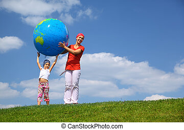 Girl lifts an inflatable globe upwards and  mother  helps daughter to hold him, upright on  grass