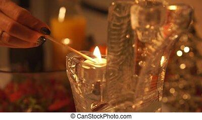 Girl light a Candle on a Christmas Wreath.