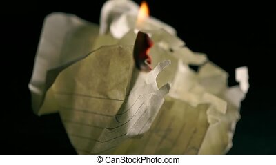 Girl lighting up and burning a piece of crumpled paper. Secret concept
