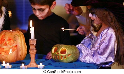 Girl lights a candle in a monster pumpkin - A girl in a ...