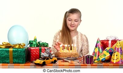 Girl lights candles on his birthday cake. Table strewn with gifts and balloons. white background