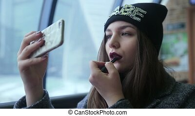 Girl lipstick looking at the phone