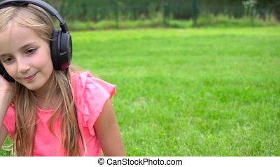girl listen music on tablet outdoors